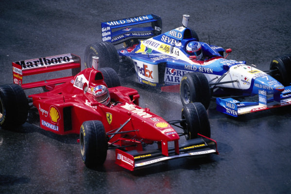 Michael Schumacher, Ferrari F310B, passes Jean Alesi, B197 Renault.