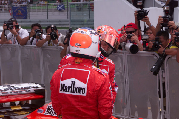 Sepang, Kuala Lumpur, Malaysia.20-22 October 2000.Rubens Barrichello congratulates team mate Michael Schumacher (both Ferrari) on qualifying on pole position, in parc ferme after qualifying.ref: digital imageWorld Copyright - LAT Photographic