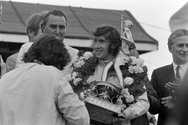 Jackie Stewart receives his winner's trophy on the podium.