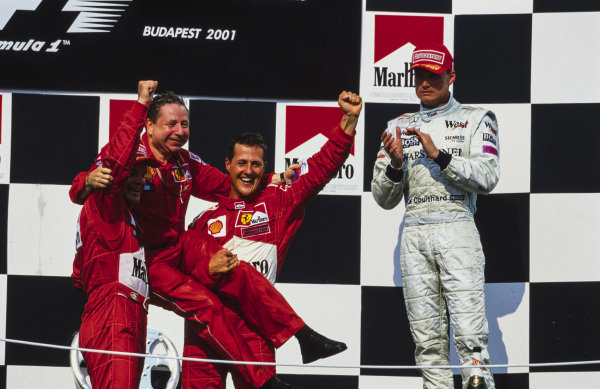 Jean Todt celebrates clinching both the constructors' and drivers' world championships on the podium with Rubens Barrichello, 2nd position, and Michael Schumacher, 1st position. A disappointed David Coulthard, 3rd position, applauds.