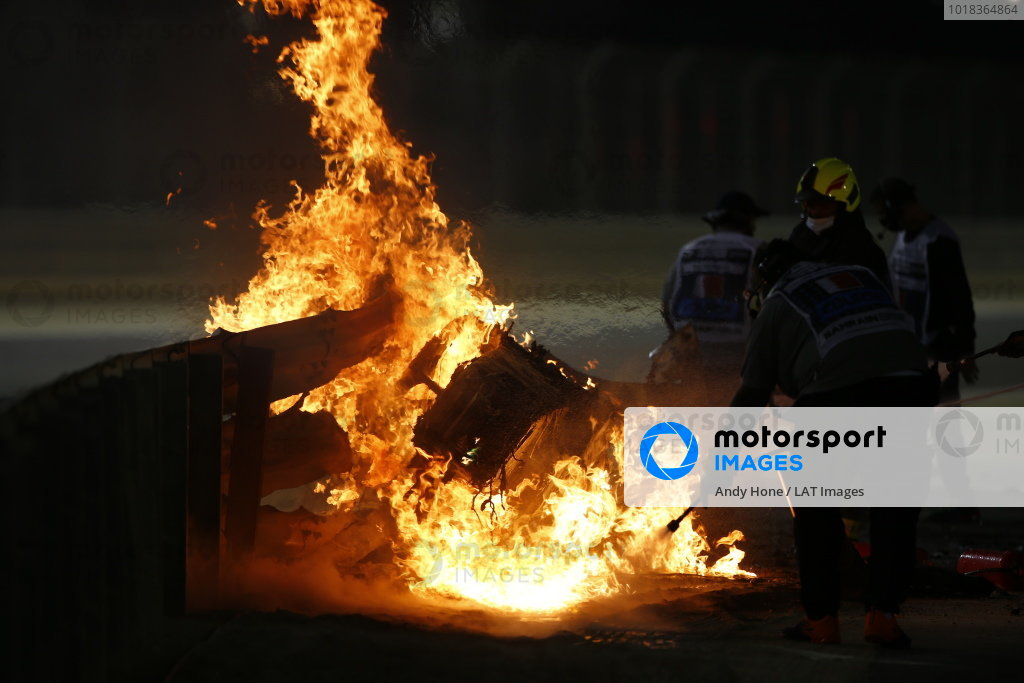 Marshals extinguish the flames after a big crash for Romain Grosjean, Haas VF-20, on the opening lap