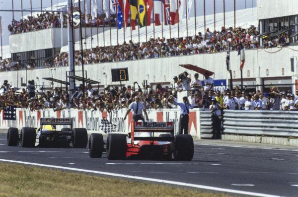 Thierry Boutsen, Williams FW13B Renault, leads Ayrton Senna, McLaren MP4-5B Honda, as the pair cross the finish line.