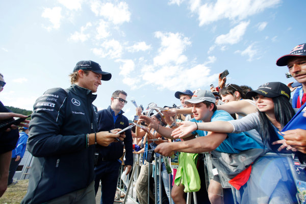 Red Bull Ring, Spielberg, Austria. Saturday 21 June 2014. Nico Rosberg, Mercedes AMG, signs autographs for fans. World Copyright: Charles Coates/LAT Photographic. ref: Digital Image _J5R9881