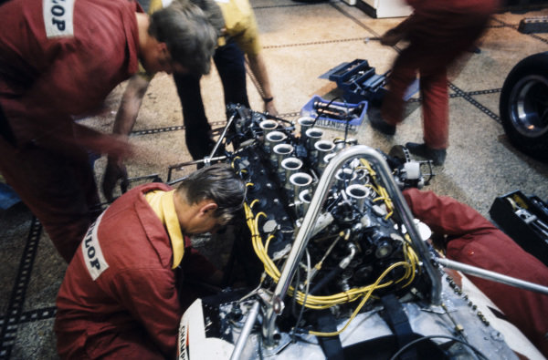 The Yardley Team BRM mechanics work on a car in the garage.
