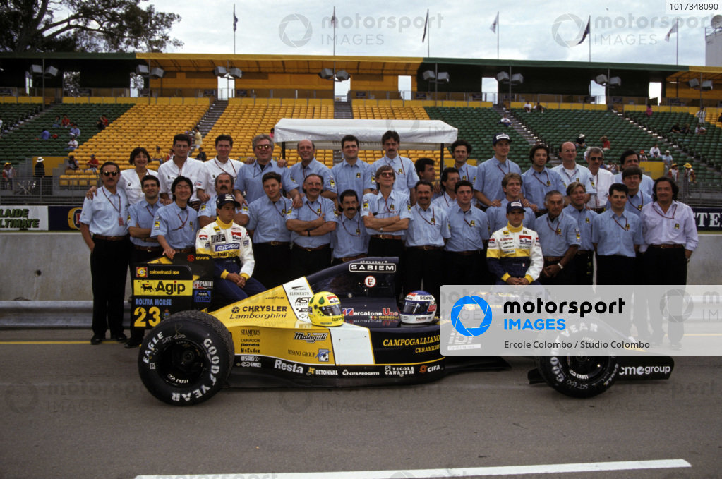 Christian Fittipaldi and Gianni Morbidelli sit on the wheels of Fittipaldi's Minardi M192 Lamborghini with the rest of the team gathered behind.