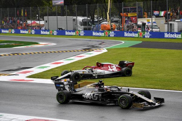 Romain Grosjean, Haas VF-19, passes as Antonio Giovinazzi, Alfa Romeo Racing C38, spins