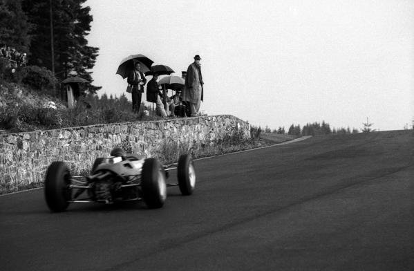 Despite the poor weather, a group of spectators have an unparalleled view of the action at the top of Eau Rouge. Belgian Grand Prix, Spa-Francorchamps, 9 June 1963.