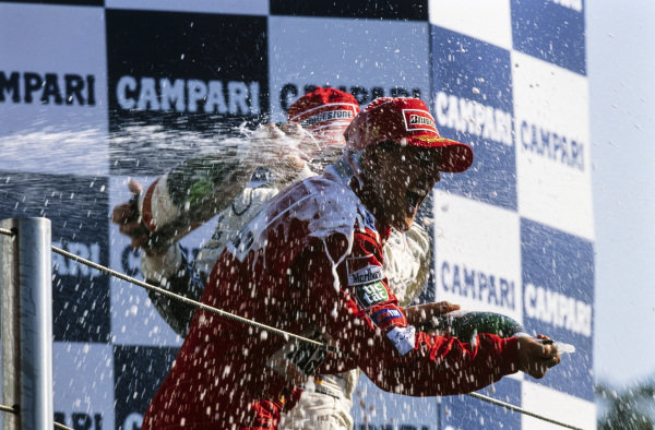 Michael Schumacher, 1st position, is blasted with champagne on the podium by his brother Ralf Schumacher, 3rd position.