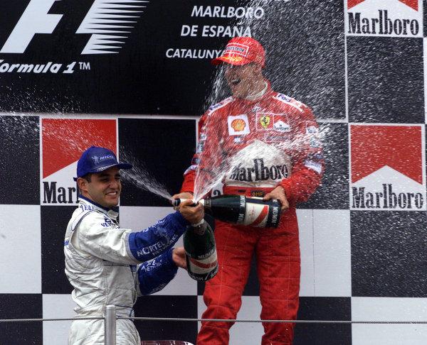 2001 Spanish Grand PrixCatalunya, Barcelona, Spain. 27-29 April 2001.Juan-Pablo Montoya (Williams BMW) 2nd position and Michael Schumacher (Ferrari) 1st position celebrate on the podium.World Copyright - Steve Etherington/LAT Photographicref: 18 mb Digital Image