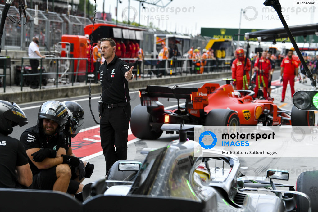 Mechanics with Lewis Hamilton, Mercedes AMG F1 W10, and Charles Leclerc, Ferrari SF90, in the pit lane