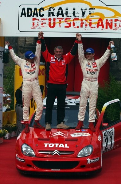 (L-R) Daniel Elena (FRA), Citroen team manager Guy Frequelin (FRA) and Sebastien Loeb (FRA) celebrate victory on the podium.