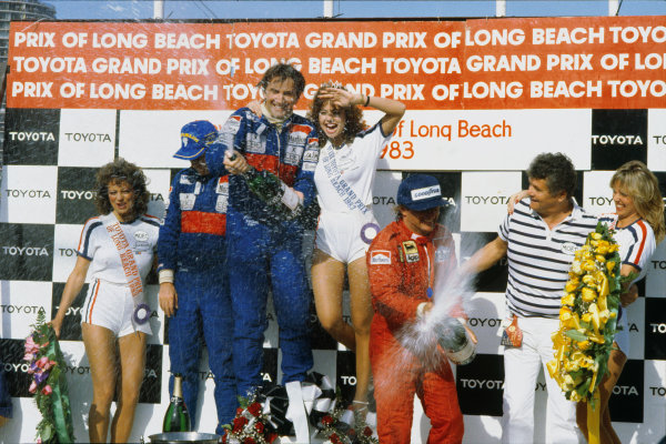 Long Beach, California, USA. 25th - 27th March 1983.John Watson (McLaren-Ford MP4/1C), 1st position, celebrates on the podium with Niki Lauda (McLaren-Ford MP4/1C), 2ndposition and Rene Arnoux (Ferrari 126C2B), 3rd position, portrait. World Copyright: LAT Photographic.Ref:  Colour Transparency.