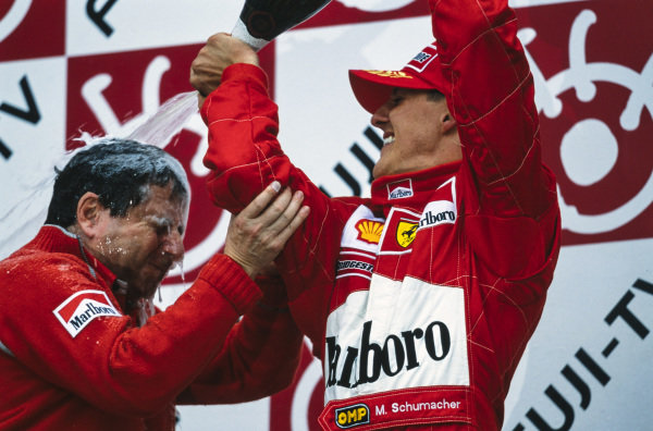 Michael Schumacher, 1st position, pours Champagne over Jean Todt, Team Principal, Ferrari, on the podium after securing the world championship.
