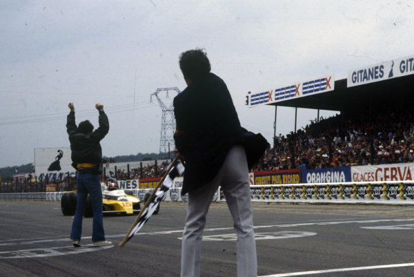 A Renault team member celebrates as Jean-Pierre Jabouille crosses the line in first in his Renault RS10 for Renault's maiden victory.