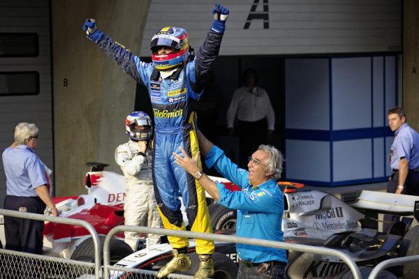 Fernando Alonso celebrates victory in parc ferme.
