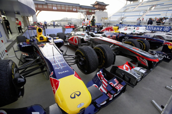 Cars in Parc Ferme, including Mark Webber's Red Bull RB7 Renault, and Lewis Hamilton's McLaren MP4-26 Mercedes.