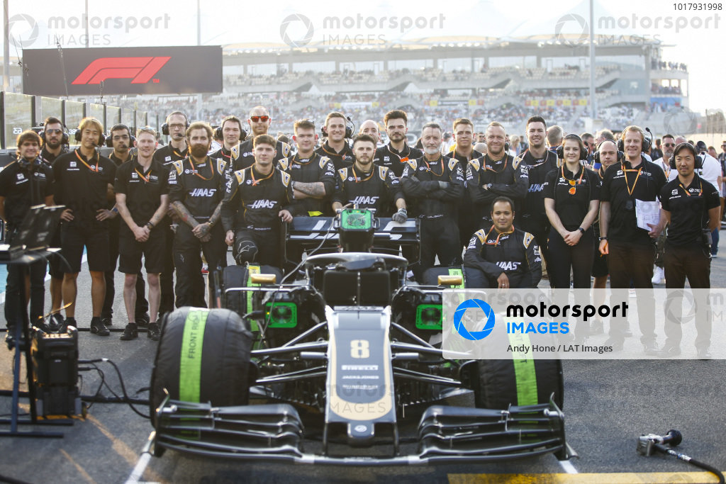 Haas mechanics pose with the Romain Grosjean Haas VF-19