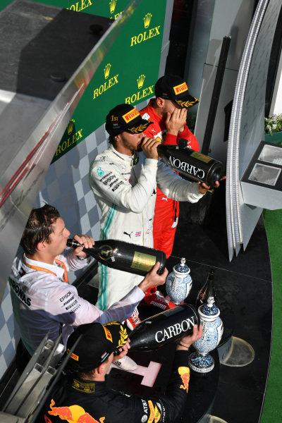 Max Verstappen, Red Bull Racing, 2nd position, Matt Deane, Chief Mechanic, Mercedes AMG, Lewis Hamilton, Mercedes AMG F1, 1st position, and Sebastian Vettel, Ferrari, 3rd position, drink Champagne on the podium
