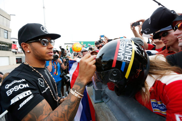 Circuit Gilles Villeneuve, Montreal, Canada. Sunday 7 June 2015. Lewis Hamilton, Mercedes AMG, 1st Position, celebrates with and signs autographs for fans. World Copyright: Alastair Staley/LAT Photographic. ref: Digital Image _79P5871