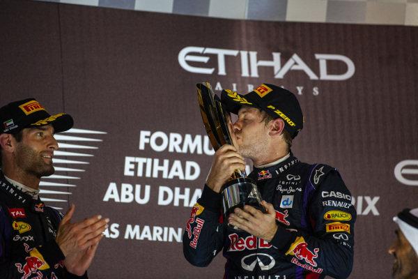 Sebastian Vettel, 1st position, kisses his trophy on the podium beside Mark Webber, 2nd position.