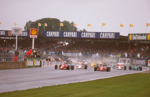 Silverstone, England. 8th - 10th July 1988. Gerhard Berger, 9th position, leads teammate Michele Alboreto (Ferrari F187/88C), retired and Ayrton Senna (McLaren MP4/4 Honda), 1st position, at the start of the race. World Copyright: LAT Photographic. Ref: 88GB25.