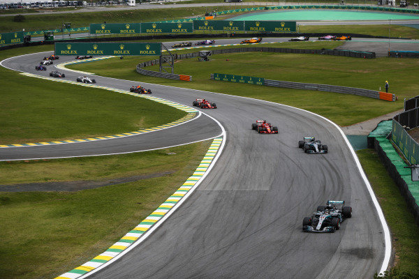 Lewis Hamilton, Mercedes AMG F1 W09, leads Valtteri Bottas, Mercedes AMG F1 W09, Sebastian Vettel, Ferrari SF71H, Kimi Raikkonen, Ferrari SF71H, Max Verstappen, Red Bull Racing RB14 Tag Heuer, and the rest of the pack.