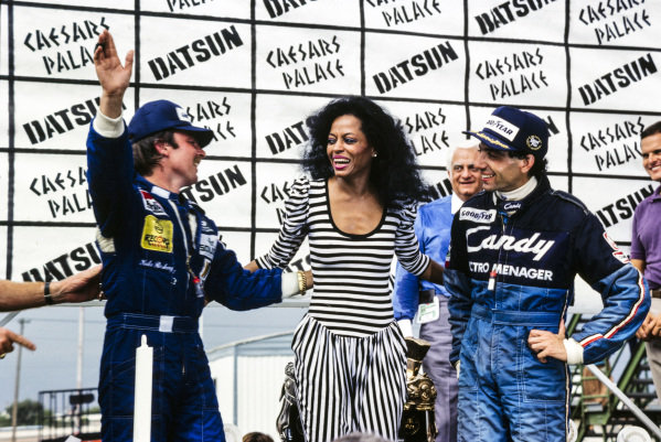 Newly-crowned world champion Keke Rosberg with Diana Ross and Michele Alboreto, 1st position, on the podium.