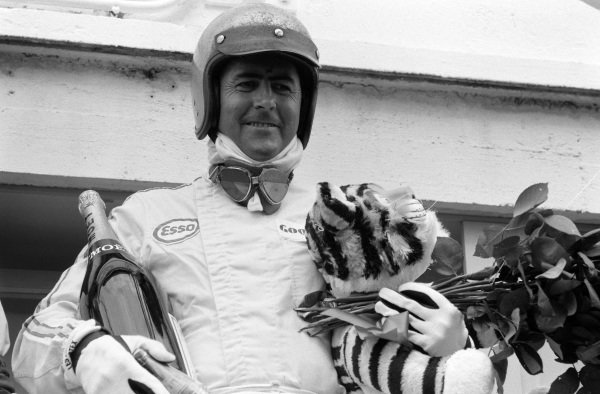 Race winner Jack Brabham celebrates on the podium with flowers, champagne and the Esso tiger mascot.