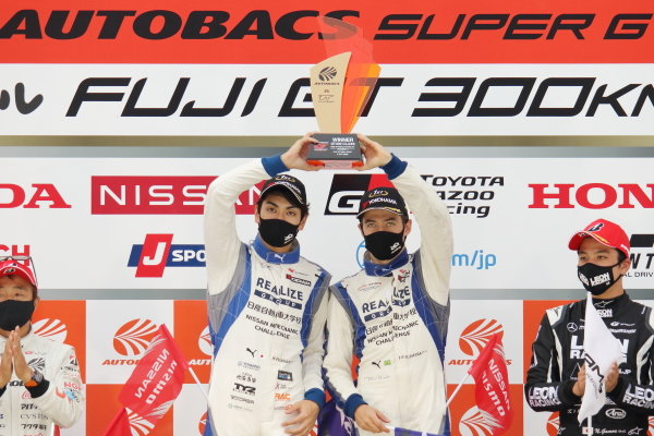 GT300 Winners Kiyoto Fujinami and João Paulo de Oliveira ( #56 Realize Nissan Automobile Technical College Nissan GT-R ) celebrate on the podium with their trophy