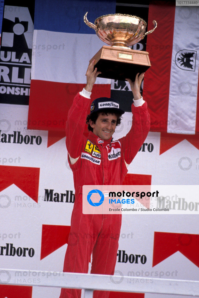 Alain Prost holds the winner's trophy aloft.