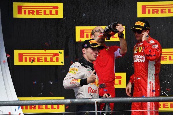 (L až R): Max Verstappen, Red Bull Racing, Carlo Santi, Ferrari Race Engineer a víťaz závodov Kimi Raikkonen, Ferrari oslavujú so šampanským na pódiu s trofejou