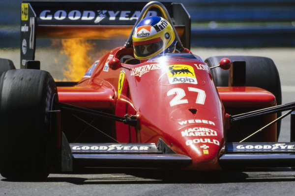 Michele Alboreto, Ferrari 156/85, with flames at the rear of the car.
