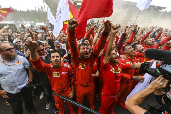 The Ferrari team celebrate below the podium