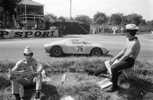 Fans sit by the side of the track as Pierre Dumay / Gustave Gosselin, Ferrari 250LM, passes.
