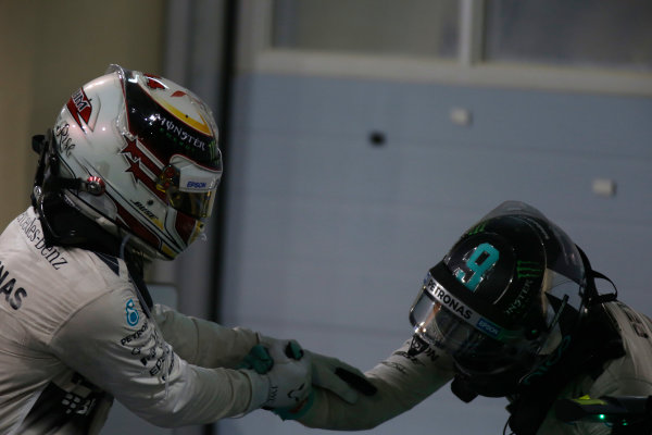 Bahrain International Circuit, Sakhir, Bahrain. Sunday 19 April 2015. Lewis Hamilton, Mercedes AMG, 1st Position, and Nico Rosberg, Mercedes AMG, 3rd Position, congratulate each other in Parc Ferme. World Copyright: Glenn Dunbar/LAT Photographic. ref: Digital Image _89P1156