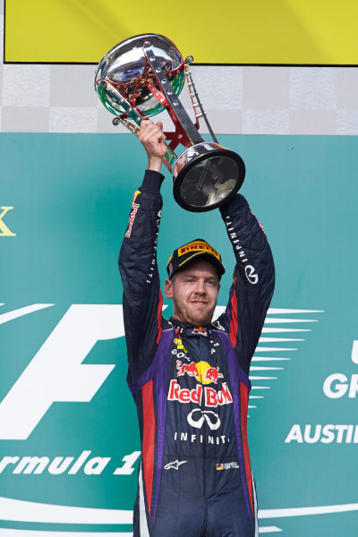 Circuit of the Americas, Austin, Texas, United States of America. Sunday 17th November 2013.  Sebastian Vettel, Red Bull Racing, 1st position, lifts his trophy on the podium. World Copyright: Steve Etherington/LAT Photographic. ref: Digital Image SNE28044 copy