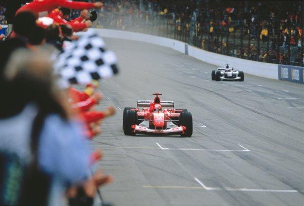 2003 United States Grand Prix Indianapolis, USA. 26th - 28th October 2003 MICHAEL SCHUMACHER, FERRARI F2003 GA, winning. Chequered Flag. Action. Minardi World Copyright: Charles Coates / LAT Photographic  ref: 35mm Image 03AMER04