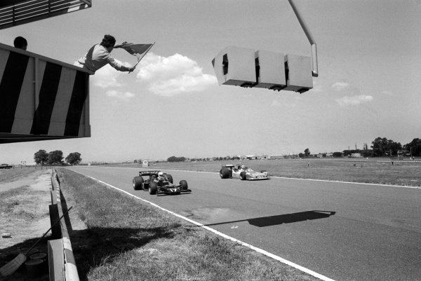 A marshal waves a flag at Renzo Zorzi (ITA) Shadow DN5B (Left) and Ian Scheckter (RSA) March 761B.