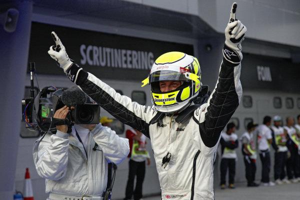 Jenson Button celebrates his pole position in parc ferme.