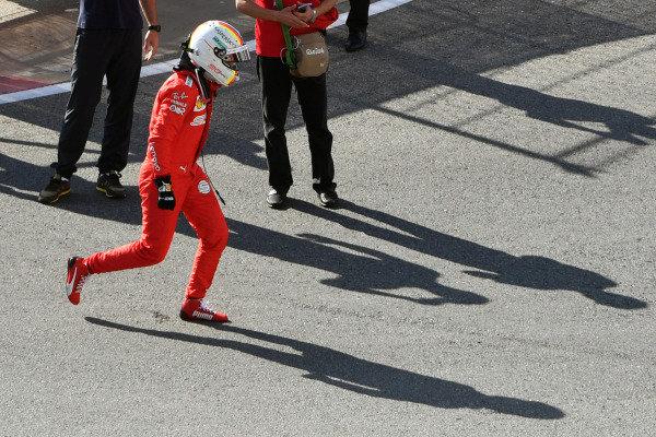 Sebastian Vettel, Ferrari, hops in frustration after retiring from the race with car trouble